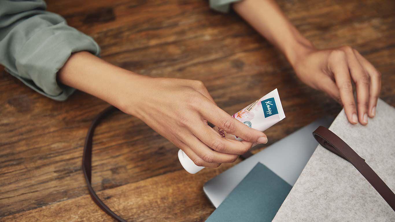 Nachaufnahme von Händen, die eine Handcremetube in eine Tasche mit Unterlagen steckt.