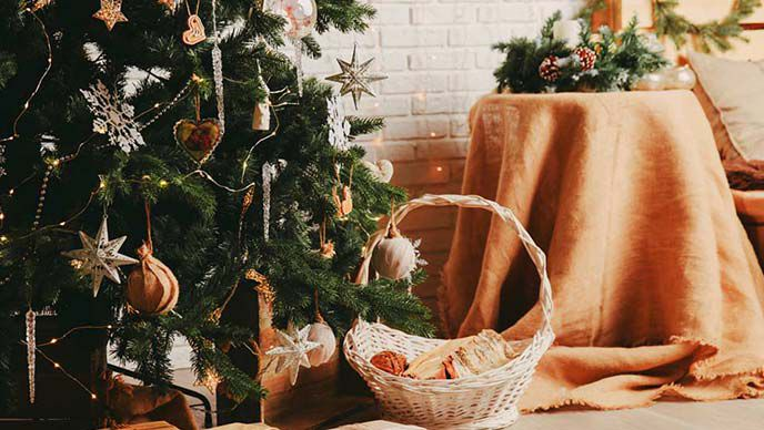 Geschmückter Weihnachtsbaum, daneben ein Holzkorb mit Geschenken.