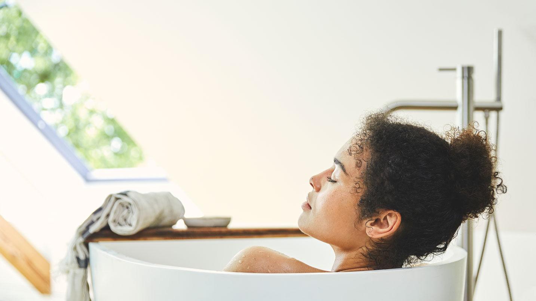 Eine Frau entspannt mit geschlossenen Augen in der Badewanne