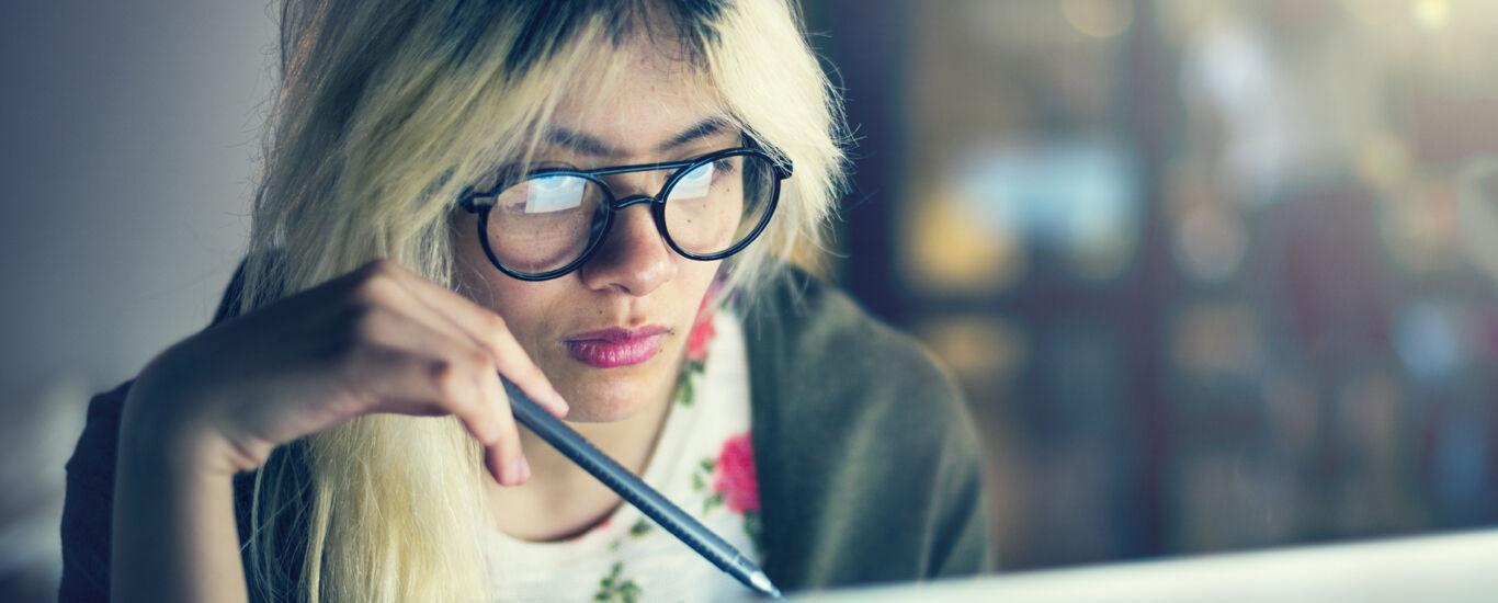 Frau sitzt vor einem PC.