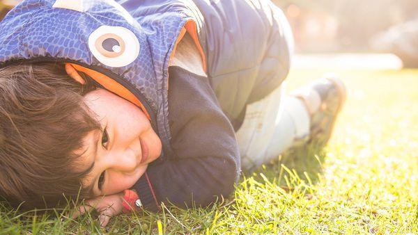 Kind duckt sich lachend auf den Boden.