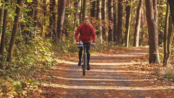Mann in Trainingsklamotten fährt Fahrrad im Wald.