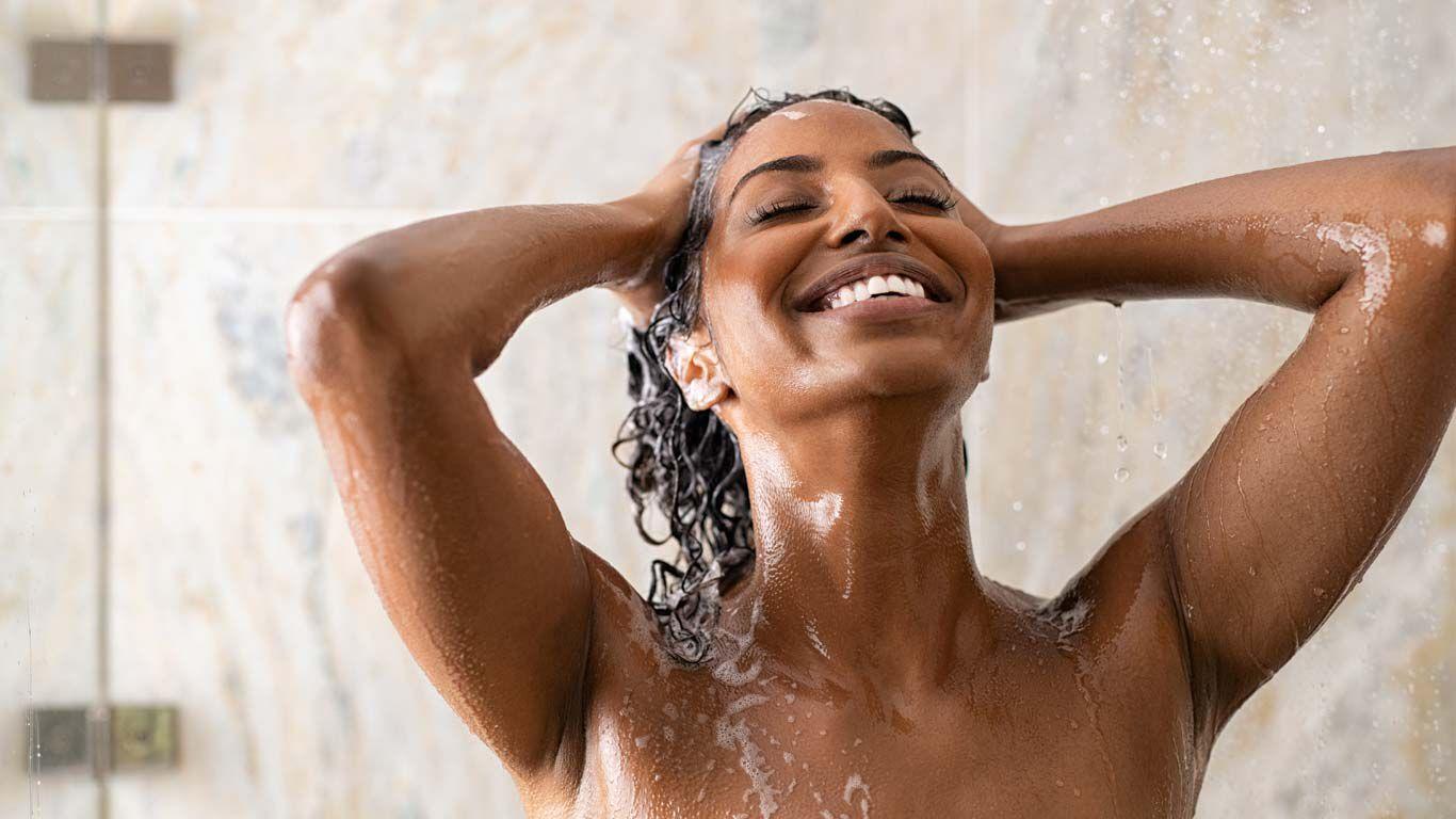 Frau lachend unter der Dusche. Kopf nach hinten gebeugt und Haare einschäumend.