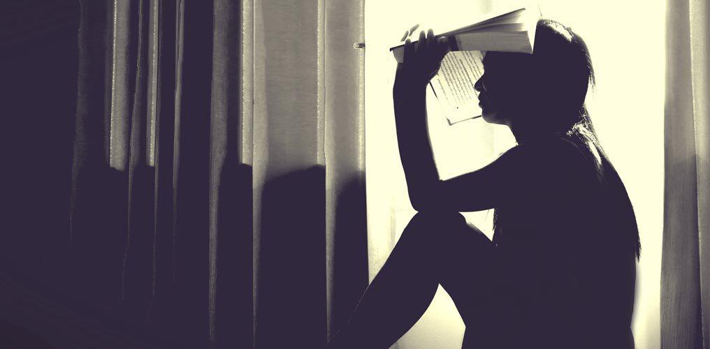 Frau sitzt auf Fensterbank und hält Buch über dem Kopf.