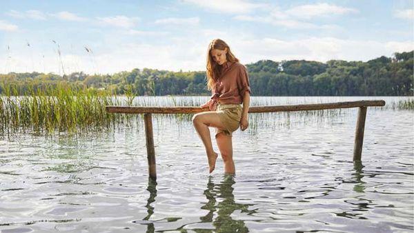 Frau beim Wassertreten in einem See mit hölzernem Handlauf.
