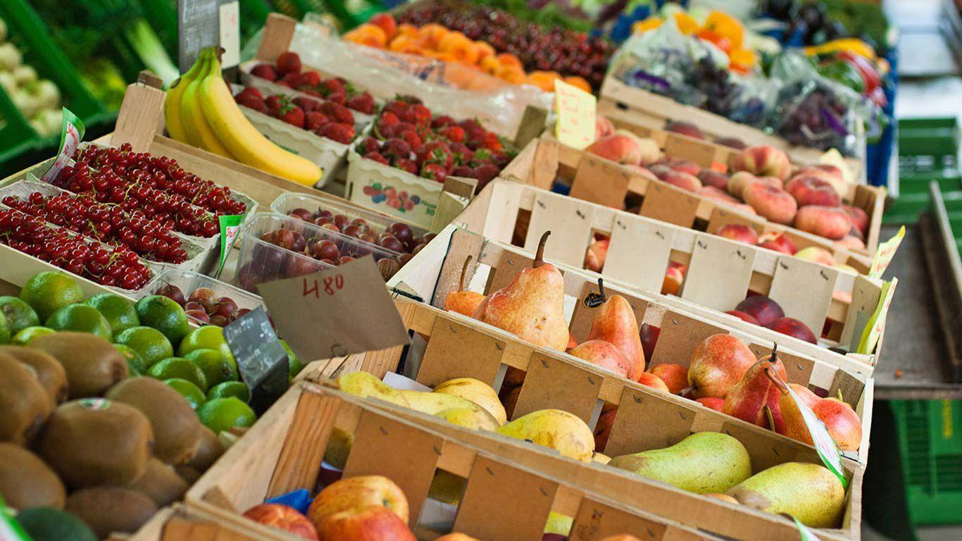 Buntes Obst in Holzkisten an einem Marktstand.