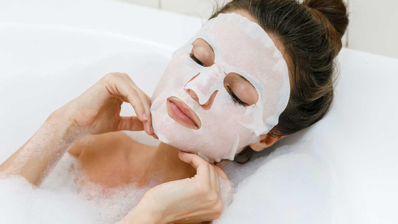 Frau entspannt mit der Tuchmaske Chill Out in der Badewanne