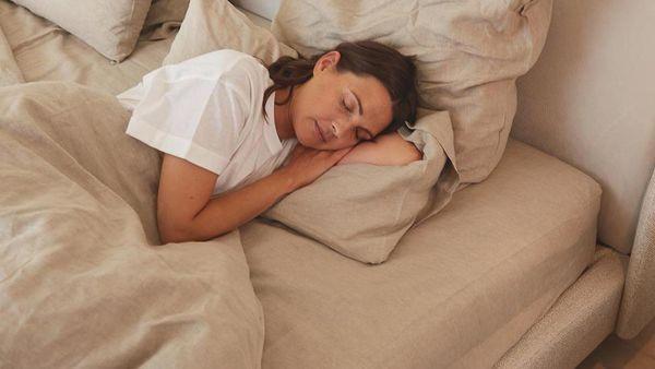 Dunkelhaarige Frau in weißem T-Shirt schläft in Bett mit beigem Leinenüberzug.