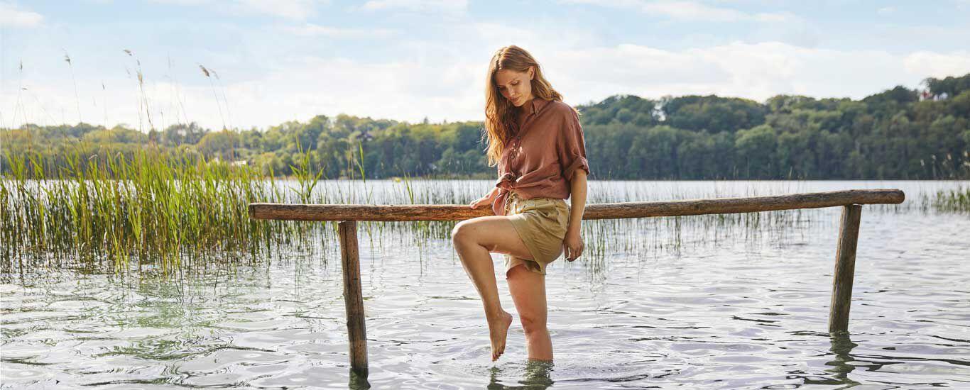 Eine Frau steht bis fast zum Knie in einem See und symbolisiert das Wassertreten.