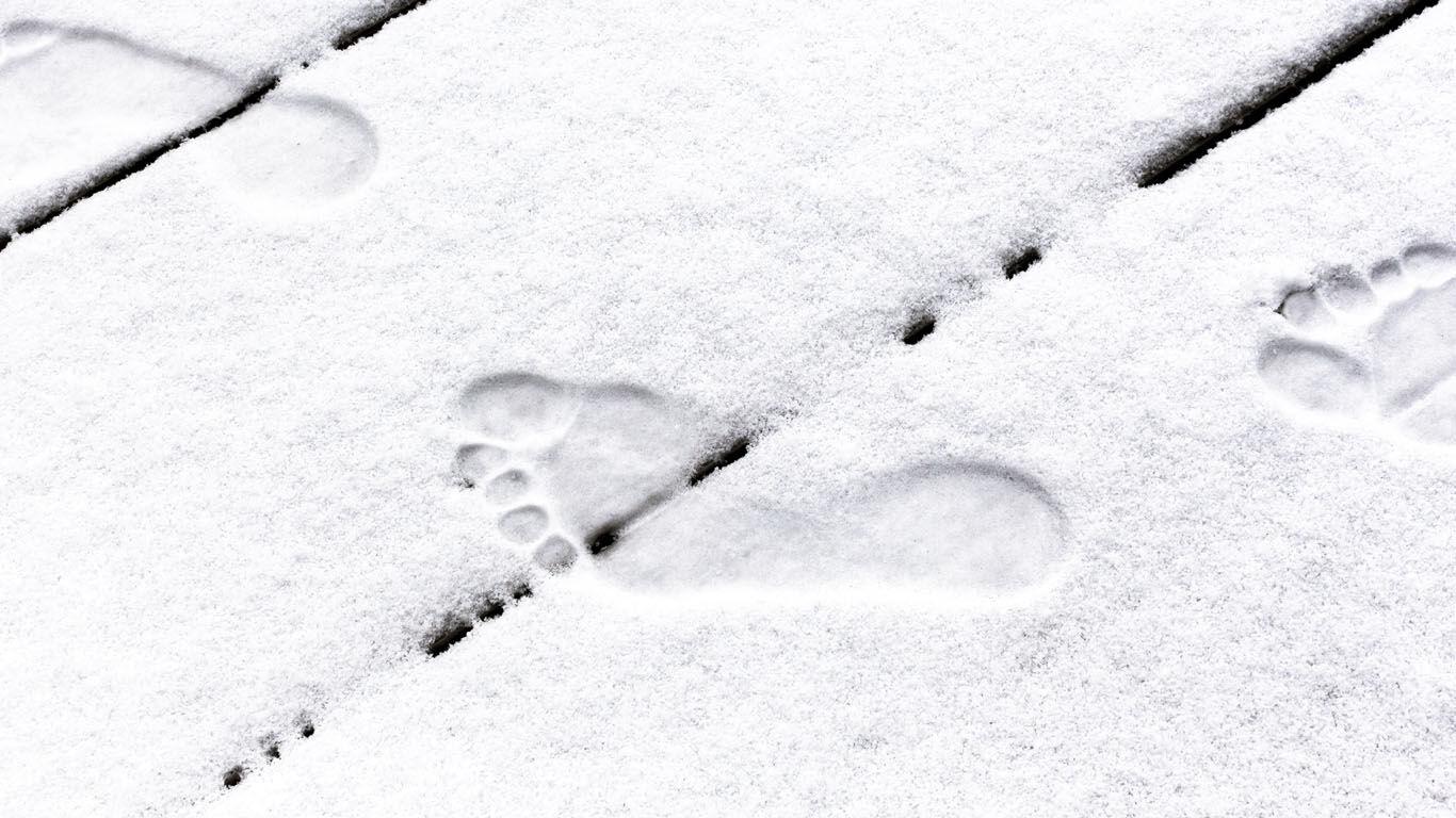 Schneebedeckter Boden, in dem man Abdrücke von Füßen erkennen kann.