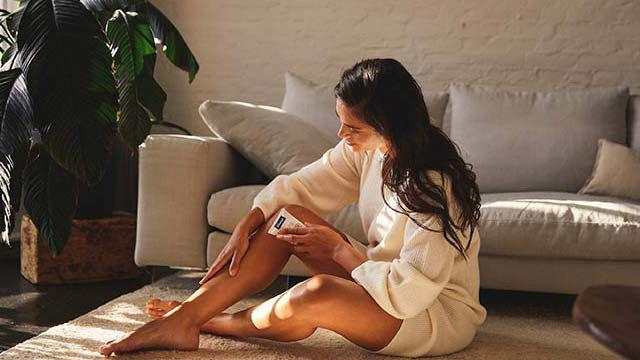 Dunkelhaarige Frau sitzt auf einem Teppich im Wohnzimmer und cremt ihre Beine ein.
