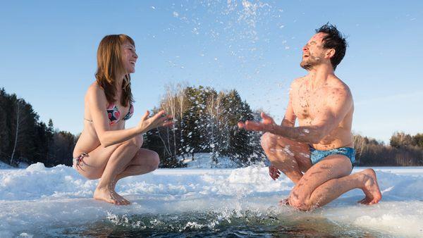 Mann und Frau knien in Badeklamotten auf winterlichem Eis und bespritzen sich gegenseitig mit Wasser.