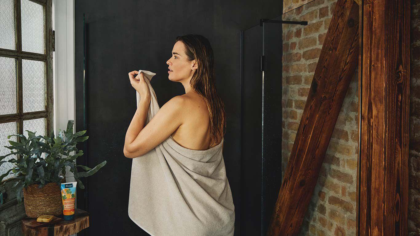 Frau in der Dusche, mit einem Handtuch umwickelt.