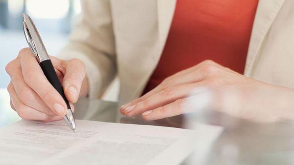 Frau in Businessklamotten unterschreibt Unterlagen.