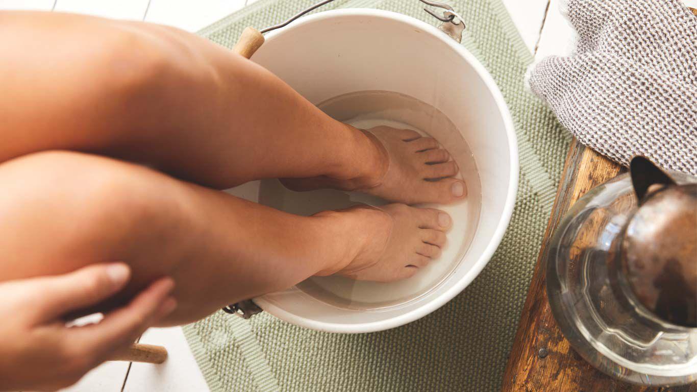 Frau hat ihre Füße in einem mit Wasser gefüllten Eimer, man sieht von ihr nur die Beine und Füße.