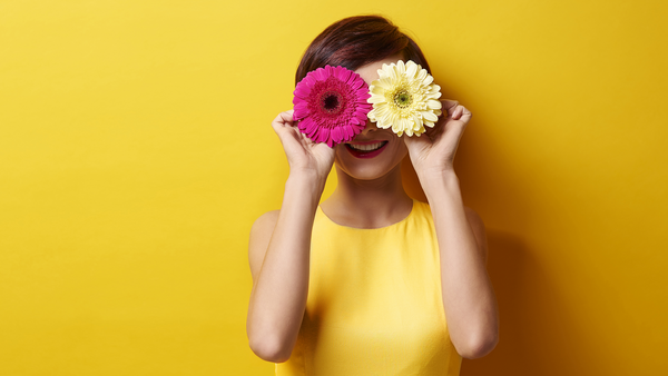 Frau in gelbem Kleid vor gelbem Hintergrund hält sich eine pinke und eine gelbe Blume vor den Augen.