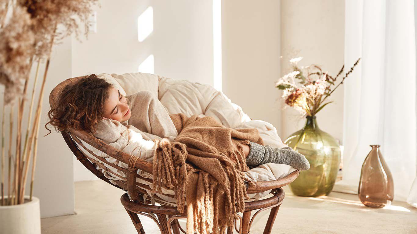 Dunkelhaarige Frau liegt auf einem gemütlichen Korbstuhl mit dicker Wolldecke.