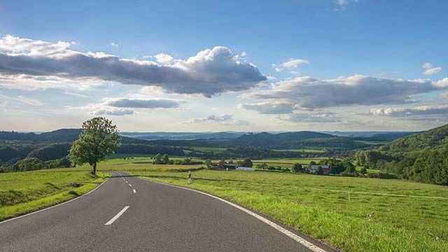 Straße, die durch grünes Land verläuft.