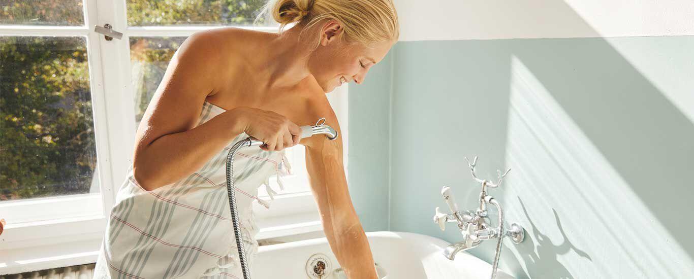 Eine Frau lässt über der Badewanne Wasser über ihren Arm laufen.