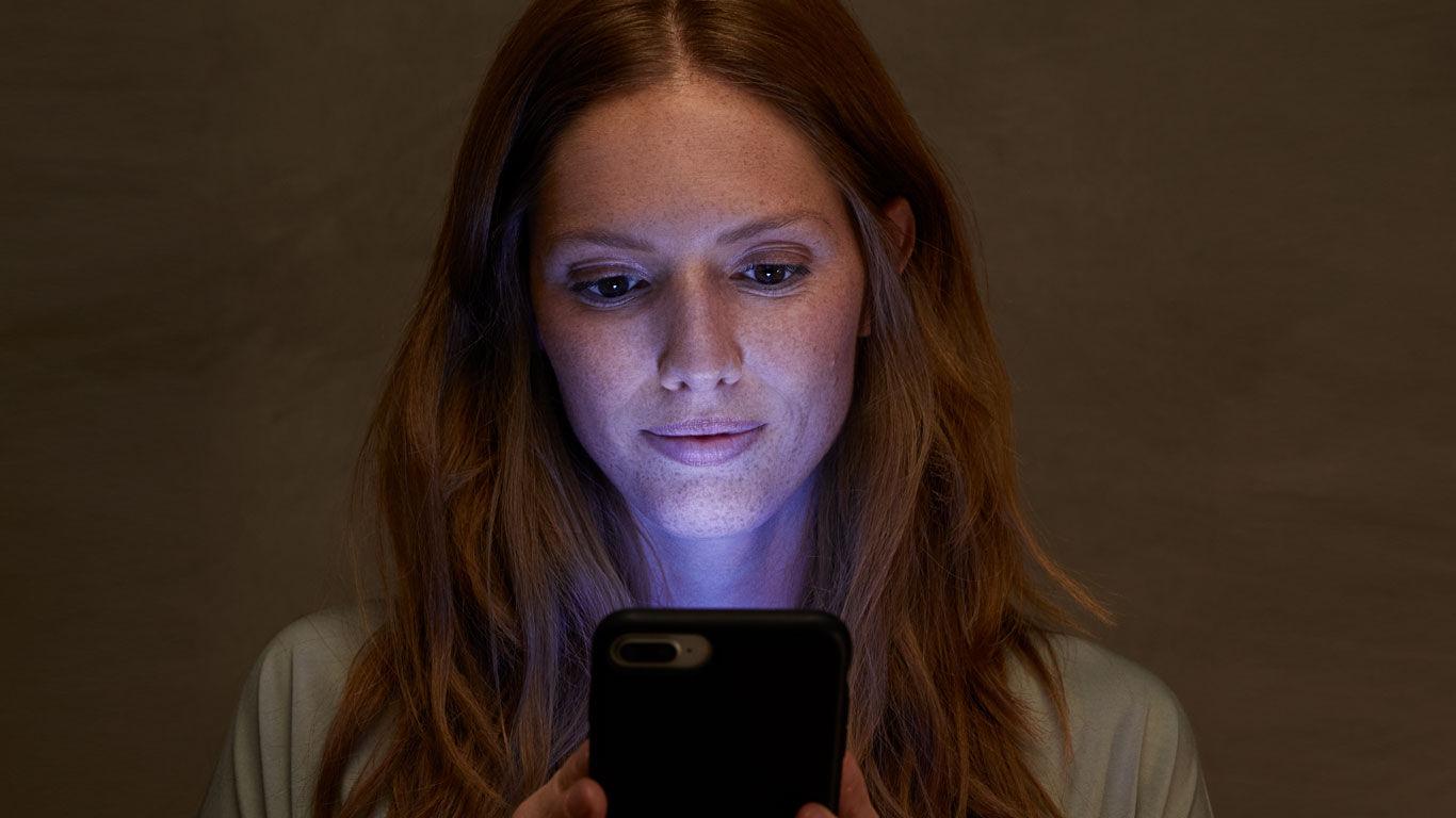 Junge Frau blickt auf Handy, dessen Bildschirm künstliches Blaulicht ausstrahlt