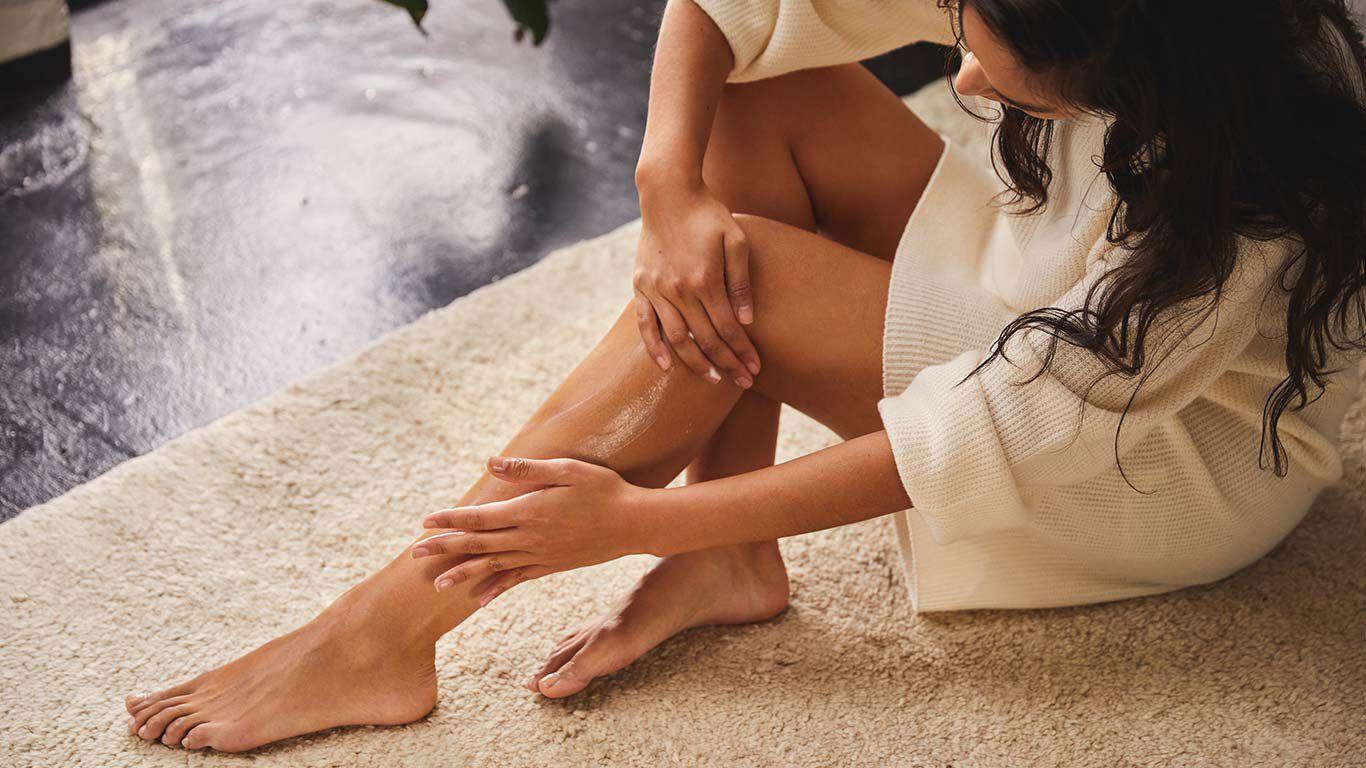 Dunkelhaarige Frau sitzt auf einem beigen Teppich und cremt ihre Beine ein.