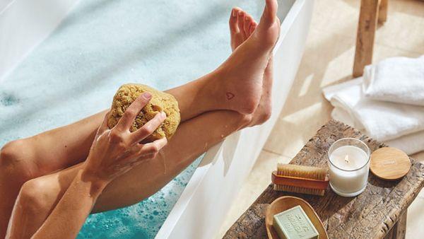 Frau sitzt in der Badewanne, die Beine auf der Kante und wäscht sich mit einem Naturschwamm.