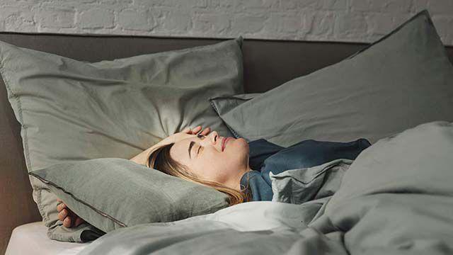 Frau liegt im Bett und genießt Sonnenstrahlen auf ihrem Gesicht.