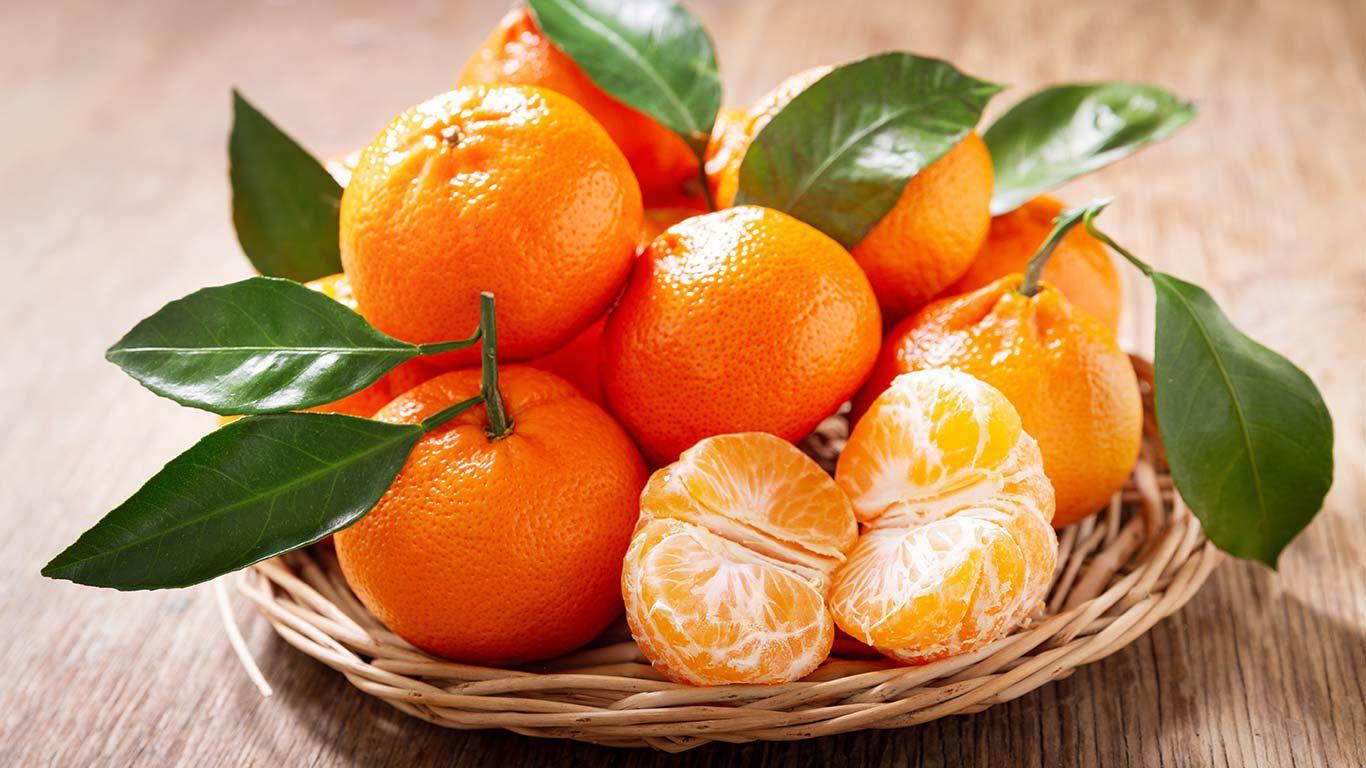 Mandarinen in einer geflochtenen Schale auf einem Tisch.