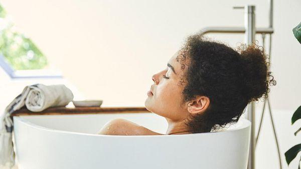 Dunkelhaarige Frau mit Locken entspannt in der Badewanne.