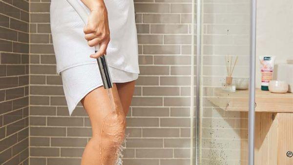 Frau im Handtuch steht in der Dusche und führt einen Knieguss durch.