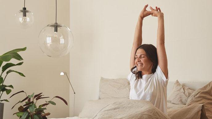 Braunhaarige Frau in weißem T-Shirt streckt sich im Bett mit beigem Leinenbezug.