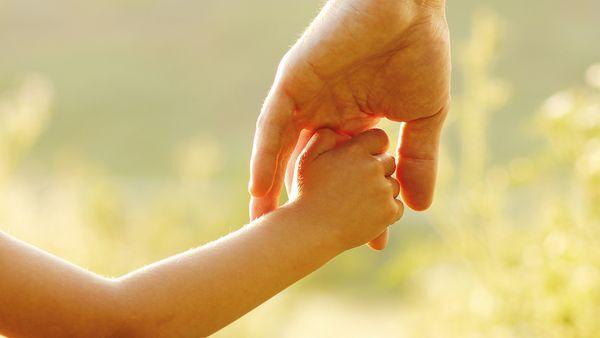 Kinderhand greift Hand eines Erwachsenen.