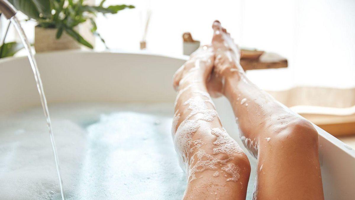 Frau liegt in der Badewanne und legt ihre Beine auf die Kante der Wanne.